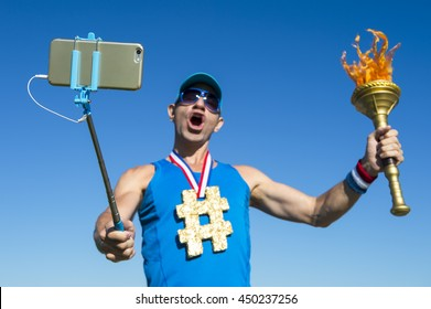 Hashtag gold medal torchbearer athlete celebrating with a selfie with a sport torch against bright blue sky