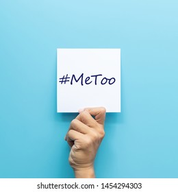 hashtag MeToo on white paper in hand isolated on blue background. MeToo is a campaign for movement against sexual harassment and sexual assault.