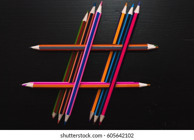 Hashtag of pencils. stacked colored pencils on the black table dark wooden surface