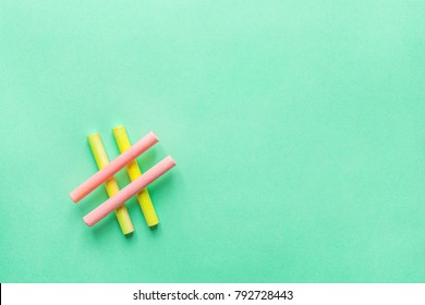 Hashtag Sign Made from Crossed Colorful Pink Yellow Chalks Crayons on Turquoise Background. Social Media Networking Blogging Concept. Female Girlish Funky Hipster Style. Pastel Colors Copyspace