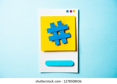 Hashtag symbol post note with paper smart phone concept on blue background. Social media and digital marketing concept. Concept of social media trends.