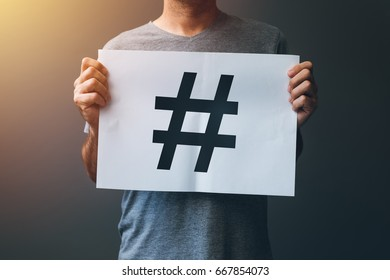 Hashtag as viral web social media network concept for marketing, trending, blogging and internet themes. Man holding paper with hash tag symbol.