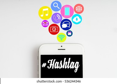 """""""#hashtag"""" words on smartphone with social media icon with white background - business, finance and copy space concept"""