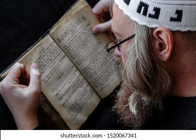 A Hasidic Jew reads Siddur. Religious orthodox Jew with a red beard and with pace in a white crocheted bale praying. Closeup