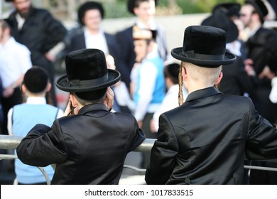 Hasidic ultra orthodox Jewish children look on in a crowd of Hasidim, while wearing fut hats and silk clothes