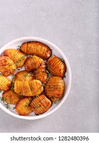 Hasselback potatoes with thyme in a plate