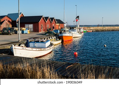 HASSLO, SWEDEN - APRIL 19, 2014: Typical small fishing harbor in southern Sweden. Early morning sunshine. Two fishermen by the boathouses. Calm weather.