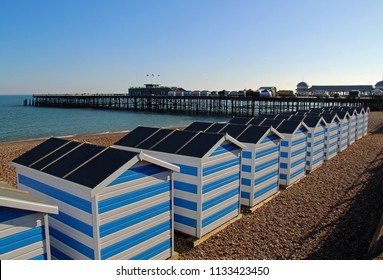 Hastings, East Sussex/UK 05-05-18 Hastings pier viewed from the promenade, along a line of blue and white beach huts, as the sun sets on a beautiful spring day