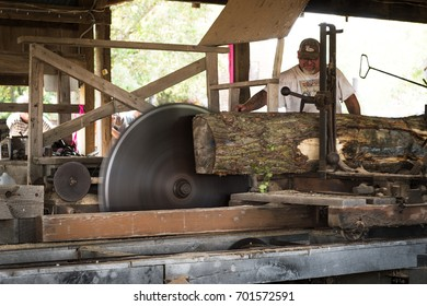 HASTINGS, MN - JULY 30, 2017: Saw operator feeds wood through steam powered sawmill at steam threshing event. Steam powered machines were in common usage throughout the 1800s and into the 1900s.