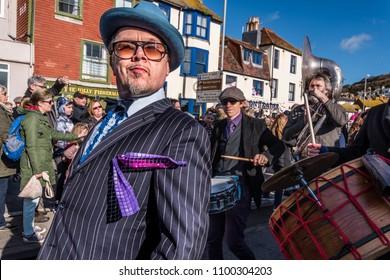 Hastings UK 02/11/2018 dapper man in hat leading Fat Tuesday Mardi Gras umbrella parade procession