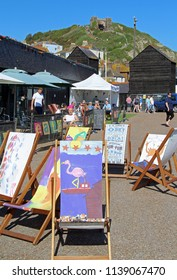 Hastings,East Sussex/UK 05-06-18 Some very colourful artistic deckchairs on The Stade public space give a pretty foreground to the East Hill lift with its funicular railway in the background