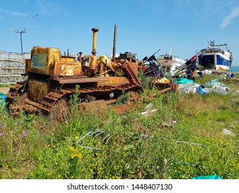 Hastings,East Sussex/UK 06-29-19 Hastings fishing beach . A rusty JCB sits on the shingle beach with fishing equipment and fishing boats behind. A view towards the English channel on a beautiful day