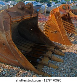 Hastings,East Sussex/UK 09-13-18 On Hastings beach 2 rusty JCB excavator buckets. They are being used for moving the huge chunks of granite being used to repair the harbour arm