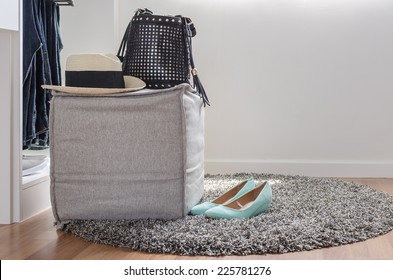 hat and bag on chair with shoes on carpet at home