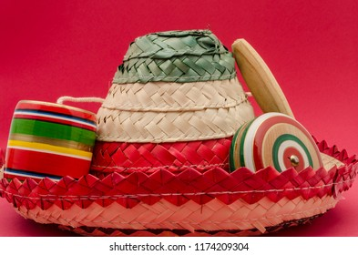 Hat, balero and yo-yo against red background. Objects for Mexican Independence Day