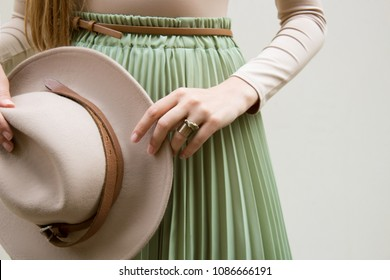 Hat, beige blouse and turqoise pleats skirt on light street backgraund.  Fashion and stylish concept.