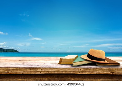 hat and book on wood terrace over tropical island beach background.
