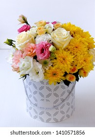 hat box with flowers: white eustoma, pink eustoma, yellow one-headed roses, yellow Bush roses, yellow chrysanthemums, green close-up on a white wooden table with a blurred background