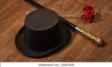hat, cane and rose on a wooden floor