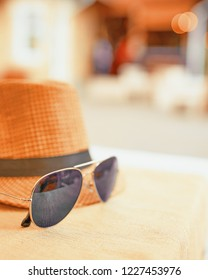 Hat and dark sunglasses on a hot day off on the table. Resort concept