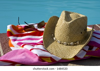 Hat, glasses and a beach towel beside a pool
