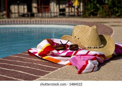 Hat, glasses and beach towel laying on the edge of a pool
