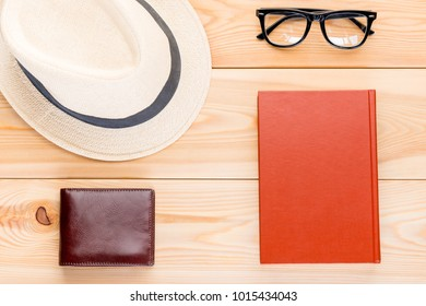 Hat, glasses, interesting book and wallet with money on wooden boards top viewHat, glasses, interesting book and wallet with money on wooden boards top view