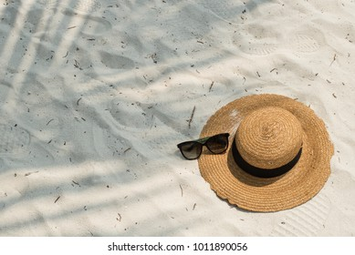 Hat and glasses on the beach at ocean Maldives, top view