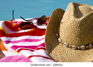 Hat, glasses and towel by a pool