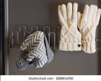 Hat and gloves drying. Gray hat and white gloves. Winter clothes are drying. Winter clothes after washing. Clean winter clothes. Hat and gloves. Modern drying cabinet.