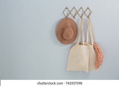 Hat, grocery bag and scarf hanging on hook against white wall