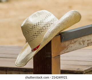 Hat hanging on a wood fence post on an agriculture farm field.