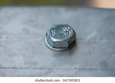 hat of a metal bolt twisted in a metal surface with a nut