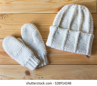 Hat and mittens connected by hand from wool on wooden background