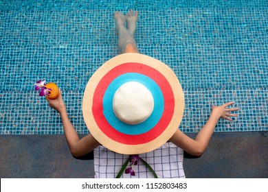 hat on head of woman sitting in swimming pool enjoy and relax with orange in hand, feel comfortable in long holidays or summer vacation