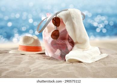 hat on sand towel and bag