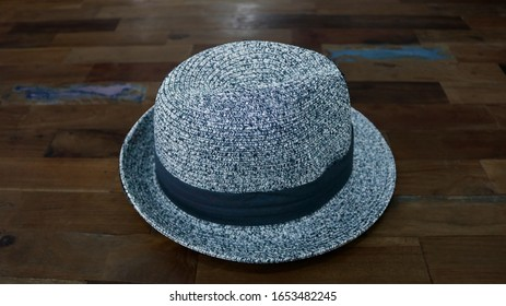 Hat on table. Mockup white hat on table. A classic gray and black hat with a black ribbon in the middle. Photo of cloth and accessory for wallpaper, cover, banner, poster, advertising, presentation