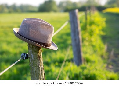 hat on top of a fence post in the fields