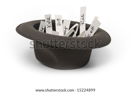 Hat on a white background filled with pieces of paper with names written on them