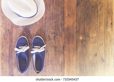 Hat and a Pair of Shoes on Wooden Surface with Copy Space
