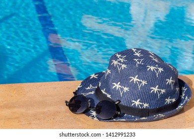 Hat with palm trees and trendy sunglasses on a poolside. Tropical resort vacation background with copy space.