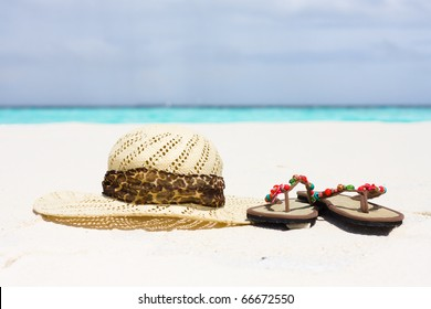 A hat and sandals lie on sand
