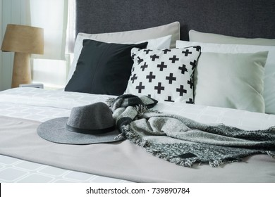 Hat and scarf setting on bed with black and white pillows in background