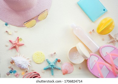 hat slippers notebook and skin cream  out of focus with soft blur on the textured light background yellow background with blurshells top view