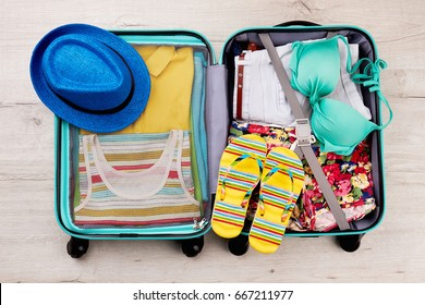 Hat and slippers on packed suitcase. Ready luggage with beach accessories for summer trip.