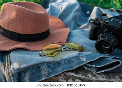 hat, sunglasses and camera on a denim jacket on a green grass/ sunny tonning