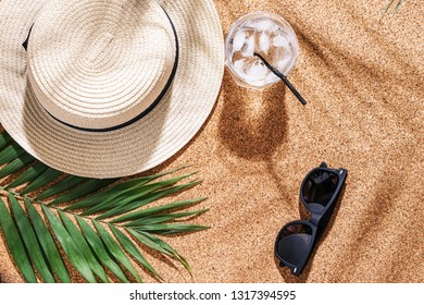 Hat with sunglasses, cold cocktail and tropical leaf on cork background