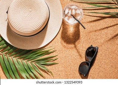 Hat with sunglasses, cold cocktail and tropical leaves on cork background