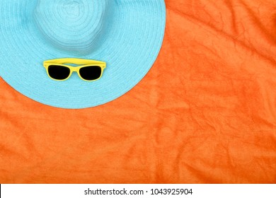 hat and sunglasses on orange beach towel with copy space