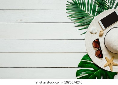 Hat, sunglasses, smartphone, sea star, green plam leaves arranged on wooden baclground. Summer holidays vacation concept. Poster banner, postcard template.